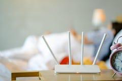 Ασύρματος δρομολογητής και ένας νεαρός άνδρας που χρησιμοποιούν ένα smartphone στην κρεβατοκάμαρα στοκ εικόνα