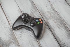 Ασύρματος μαύρος ελεγκτής gamepad ή παιχνιδιών για το τυχερό παιχνίδι κονσολών στον άσπρο ξύλινο πίνακα Στοκ Εικόνες