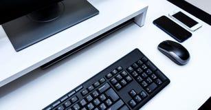 Ασύρματο ποντίκι υπολογιστών, μαύρο όργανο ελέγχου, πληκτρολόγιο και δύο κινητά τηλέφωνα σε ένα άσπρο γραφείο Στοκ εικόνες με δικαίωμα ελεύθερης χρήσης