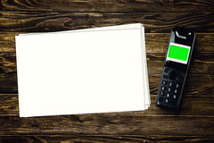 Ασύρματο τηλέφωνο και κενό έγγραφο για tabletop Στοκ Εικόνες
