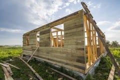 Ατελές οικολογικό σπίτι κάτω από την κατασκευή στον πράσινο τομέα στο υπόβαθρο μπλε ουρανού Τάφροι που γεμίζουν με το τσιμέντο κα στοκ φωτογραφία