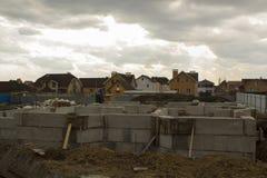 Ατελής κατασκευή του καινούργιου σπιτιού ενάντια στα ήδη χτισμένα σπίτια Έννοια οικοδόμησης στοκ φωτογραφία με δικαίωμα ελεύθερης χρήσης