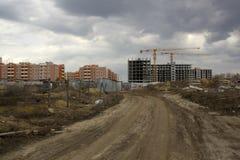 Ατελής οικοδόμηση κτηρίου ενάντια στα ήδη χτισμένα σπίτια Έννοια οικοδόμησης στοκ εικόνες με δικαίωμα ελεύθερης χρήσης