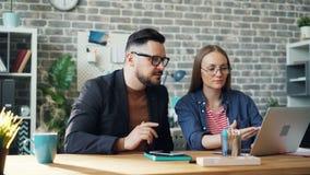 Ατελείωτος βρόχος του άνδρα και της γυναίκας που εργάζονται με το lap-top βράζοντας στον ατμό φλυτζανιών καφέ απόθεμα βίντεο