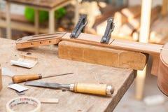 Ατελής κιθάρα στον πίνακα στο εργαστήριο με τα εργαλεία στοκ φωτογραφία με δικαίωμα ελεύθερης χρήσης