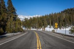 Ατελείωτος δρόμος με χιονισμένος στα δέντρα πλευράς και πεύκων στο υπόβαθρο λίμνη Καλιφόρνιας tahoe Στοκ Εικόνα