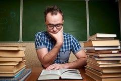 Ατημέλητος αξύριστος νεαρός άνδρας στα γυαλιά που διαβάζει ένα βιβλίο στον πίνακα με τους σωρούς των βιβλίων στοκ εικόνες