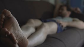 Ατημέλητο άτομο στους μπόξερ και το τοπ ύπνο δεξαμενών στον καναπέ, μη απασχόλησης ζωή, κατάθλιψη απόθεμα βίντεο