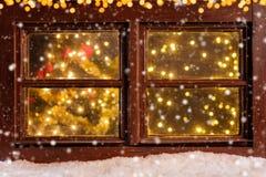 Ατμοσφαιρικό παράθυρο Χριστουγέννων με το μειωμένο χιόνι Στοκ φωτογραφία με δικαίωμα ελεύθερης χρήσης