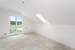 Αττικό δωμάτιο κάτω από την κατασκευή με τους πίνακες ασβεστοκονιάματος γύψου και τα παράθυρα Στοκ Φωτογραφία