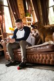 Ατόμων στον καναπέ που παίζει τα τηλεοπτικά παιχνίδια, η συνεδρίαση σκυλιών του κοντά σε τον στοκ εικόνα
