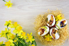 Αυγά ζωγραφικής Πάσχας στο ύφος decoupage με τους ναρκίσσους Στοκ Εικόνα