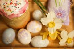 Αυγά κέικ και διακοσμήσεων Πάσχας με τα daffodils στον πίνακα Στοκ εικόνες με δικαίωμα ελεύθερης χρήσης