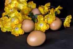 Αυγά και κίτρινες ανθοδέσμες λουλουδιών Στοκ Φωτογραφίες