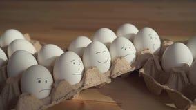 Αυγά κοτόπουλου με τα χρωματισμένα πρόσωπα σε ένα κουτί από χαρτόνι Η έννοια Πάσχας απόθεμα βίντεο