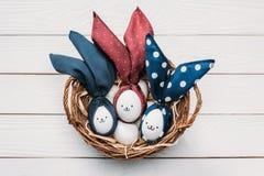 Αυγά κοτόπουλου Πάσχας με τα smileys και αυτιά λαγουδάκι στο καλάθι Στοκ εικόνες με δικαίωμα ελεύθερης χρήσης