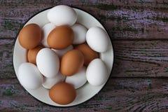 Αυγά κοτόπουλου σε ένα γυαλί και ένα πιάτο metall στους πορφυρούς πίνακες Στοκ Εικόνα