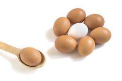 Αυγά κοτόπουλου στο άσπρο υπόβαθρο και το ξύλινο κουτάλι στοκ φωτογραφίες