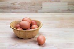Αυγά κότας στο ξύλινο κύπελλο Στοκ Φωτογραφίες
