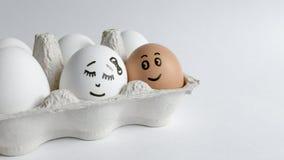 Αυγά με τα αστεία πρόσωπα στη συσκευασία σε ένα άσπρο υπόβαθρο Φωτογραφία έννοιας Πάσχας Πρόσωπα στα αυγά Στοκ Φωτογραφία