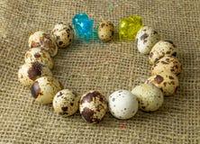 Αυγά ορτυκιών που βρίσκονται γύρω μαζί με έναν μικρό μπλε και κίτρινο ελέφαντα γυαλιού στοκ φωτογραφία
