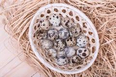 Αυγά ορτυκιών σε ένα ψάθινο καλάθι με το άχυρο, τοπ άποψη Στοκ Φωτογραφία