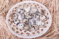 Αυγά ορτυκιών σε ένα ψάθινο καλάθι με το άχυρο Στοκ Φωτογραφίες