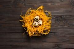 Αυγά ορτυκιών στη διακοσμητική φωλιά στο σκοτεινό ξύλινο υπόβαθρο κορυφαία όψη Στοκ Φωτογραφία
