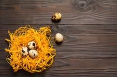 Αυγά ορτυκιών στη διακοσμητική φωλιά στο σκοτεινό ξύλινο υπόβαθρο κορυφαία όψη διάστημα αντιγράφων Στοκ φωτογραφίες με δικαίωμα ελεύθερης χρήσης