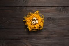 Αυγά ορτυκιών στη διακοσμητική φωλιά στο σκοτεινό ξύλινο υπόβαθρο κορυφαία όψη Στοκ εικόνες με δικαίωμα ελεύθερης χρήσης