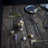 Αυγά ορτυκιών στο αγροτικό κύπελλο μετάλλων στον ξύλινο πίνακα χωρών σε διά Στοκ Εικόνες