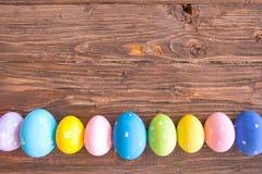 Αυγά Πάσχας Ζωηρόχρωμα αυγά Πάσχας που χρωματίζονται στα φωτεινά χρώματα στη γραμμή ή τη σειρά στο ξύλινο υπόβαθρο Στοκ Φωτογραφίες