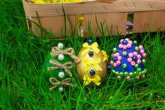 Αυγά Πάσχας και ένα καλάθι με τα λουλούδια Στοκ Εικόνες
