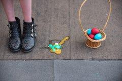 Αυγά Πάσχας και θηλυκά πόδια στις μπότες στο υπόβαθρο ασφάλτου στοκ εικόνες