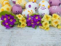 Αυγά Πάσχας και κίτρινη και ιώδης σύνθεση λουλουδιών primula Στοκ φωτογραφία με δικαίωμα ελεύθερης χρήσης