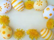 Αυγά Πάσχας και κίτρινο πλαίσιο λουλουδιών πικραλίδων Στοκ φωτογραφία με δικαίωμα ελεύθερης χρήσης
