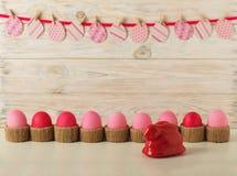 Αυγά Πάσχας και ντεκόρ Πάσχας - έγγραφο κουνελιών και αυγών με ένα ροζ Στοκ Φωτογραφίες
