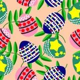 Αυγά Πάσχας και όμορφα πράσινα φύλλα στο ανοικτό πορτοκαλί υπόβαθρο Στοκ Εικόνες
