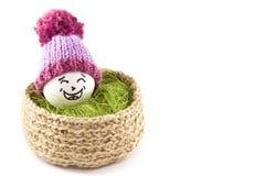 αυγά Πάσχας καλαθιών Emoticons στα πλεκτά καπέλα με τα pom-poms Στοκ Φωτογραφία