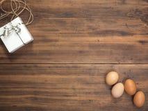 Αυγά Πάσχας, κιβώτιο δώρων στον παλαιό ξύλινο πίνακα από τις σανίδες Τοπ άποψη με το διάστημα για το σχέδιό σας, χαιρετισμοί Πάσχ Στοκ Εικόνα