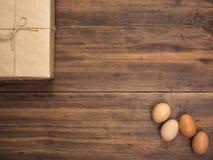 Αυγά Πάσχας, κιβώτιο δώρων στον παλαιό ξύλινο πίνακα από τις σανίδες Τοπ άποψη με το διάστημα για το σχέδιό σας, χαιρετισμοί Πάσχ Στοκ Φωτογραφία