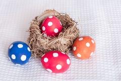 Αυγά Πάσχας κοντά στη φωλιά πουλιών στο ελεγμένο άσπρο υπόβαθρο Στοκ εικόνες με δικαίωμα ελεύθερης χρήσης