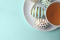 Αυγά Πάσχας με ένα φλυτζάνι του τσαγιού στο υπόβαθρο μεντών κιρκιριών aqua με το διάστημα αντιγράφων Στοκ φωτογραφία με δικαίωμα ελεύθερης χρήσης