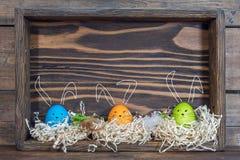 Αυγά Πάσχας με τα αυτιά λαγουδάκι στις φωλιές στα κιβώτια στοκ εικόνες