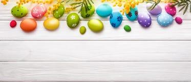 Αυγά Πάσχας με τα λουλούδια στο ξύλινο υπόβαθρο Στοκ Φωτογραφίες