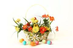 Αυγά Πάσχας με τα λουλούδια και το καλάθι Στοκ Εικόνα