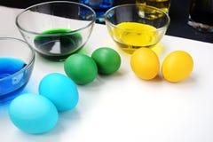 Αυγά Πάσχας με τα φλυτζάνια του χρώματος Διακοπές άνοιξη Κίτρινα, πράσινα και μπλε αυγά στοκ εικόνες με δικαίωμα ελεύθερης χρήσης