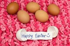 Αυγά Πάσχας με τη σημείωση στο κοχύλι στο ρόδινο υπόβαθρο υφάσματος Στοκ Φωτογραφία