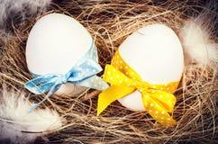 Αυγά Πάσχας με τις ζωηρόχρωμες κορδέλλες σε μια κινηματογράφηση σε πρώτο πλάνο φωλιών Στοκ Φωτογραφίες