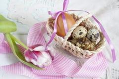 Αυγά Πάσχας με τις κορδέλλες σε ένα ψάθινο καλάθι, δίπλα στην τουλίπα Στοκ Εικόνες